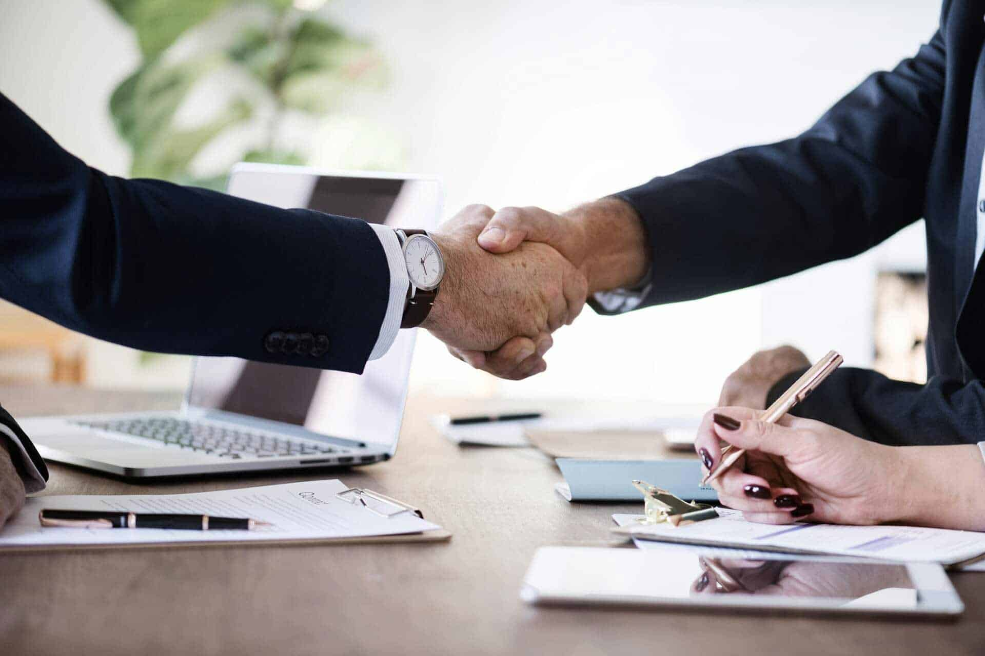 Two men shaking hands over a desk during a business deal